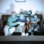 A comical photograph of a family enjoying movie night together at home.